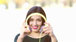 Close up of beautiful brunette woman putting on yellow headphones and listening to music, graded