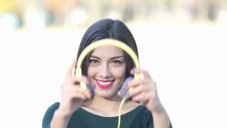 Close up of beautiful brunette woman putting on yellow headphones and listening to music