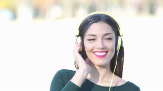 Close up of beautiful brunette woman with headphones listening to music on sunny day, slow motion