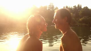 Close up of beautiful happy couple looking at each other, laughing and talking while sitting next to the Mreznica river at sunset, graded