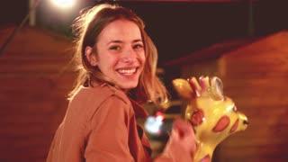 Close up of beautiful happy woman having fun riding carousel in amusement park, graded