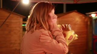 Close up of beautiful happy woman having fun riding carousel in amusement park, slow motion