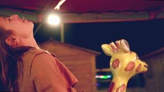 Close up of beautiful happy woman having fun riding carousel in amusement park, smiling and waving at camera, graded
