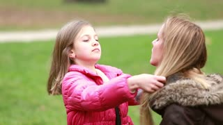Close up of beautiful little girl putting her hands through her mother's long hair in park