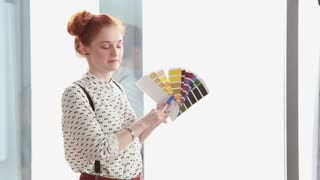 Close up of beautiful red hair woman holding color fan deck during presentation
