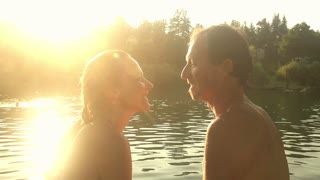 Close up of beautiful romantic couple looking at each other, smiling and talking while sitting next to the Mreznica river at sunset, graded