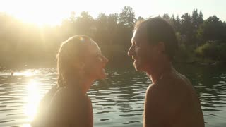 Close up of beautiful romantic couple sitting next to the Mreznica river at sunset, looking at each other, smiling and talking