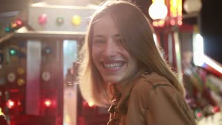 Close up of beautiful woman having fun in amusement park, waving to the camera