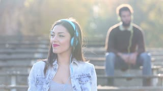 Close up of beautiful woman listening to music on headphones and smiling, man blurred in background, slow motion