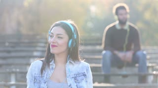 Close up of beautiful woman listening to music on headphones and smiling, man blurred in background