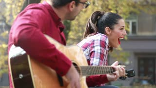 Close-up of beautiful woman singing while handsome man playing guitar, sitting next to her on bench in park, graded