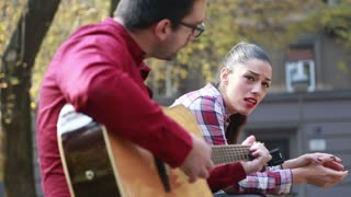 Close-up of beautiful woman singing while handsome man playing guitar, sitting next to her on bench in park