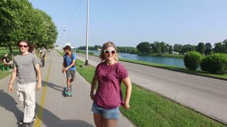 Close up of beautiful woman skateboarding with two male friends