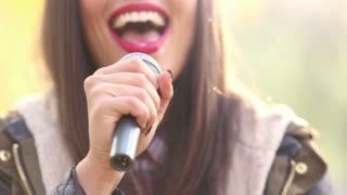 Close-up of beautiful woman's mouth with red lipstick, smiling and singing with microphone, graded