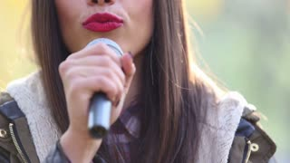 Close-up of beautiful woman's mouth with red lipstick, smiling and singing with microphone, in slow motion
