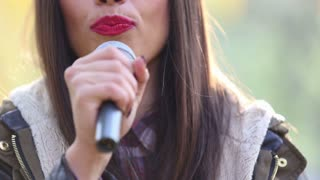 Close-up of beautiful woman's mouth with red lipstick, smiling and singing with microphone