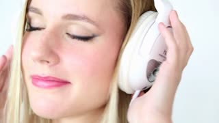 Close up of beautiful young blond woman dancing with white headphones in white bright background