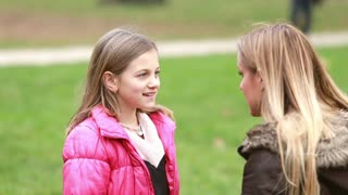 Close up of beautiful young girl talking with her mom in park