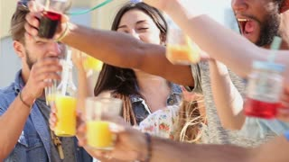 Close up of beautiful young people hanging out and toasting at rooftop party