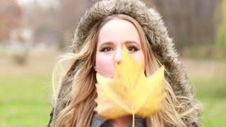 Close up of beautiful young woman holding leaf in front of the face, moving it and making funny faces