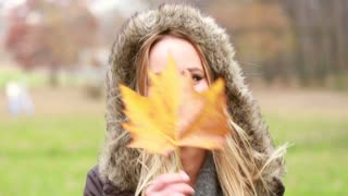 Close up of beautiful young woman playing with leaf in park