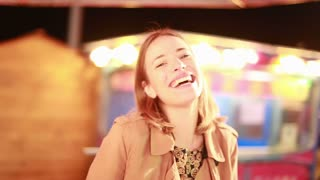 Close up of beautiful young woman riding on roundabout and beckoning to camera in amusement park