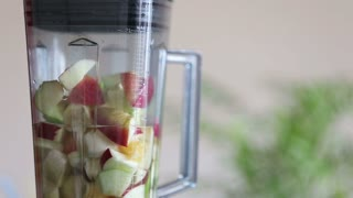 Close-up of blending pieces of fruit in blender, in slow motion