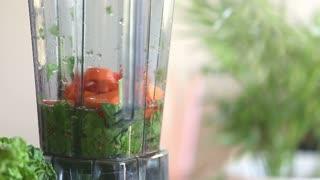 Close-up of blending vegetables in blender, in slow motion, graded