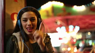 Close up of brunette girl dancing to the rhythm of music with headphones