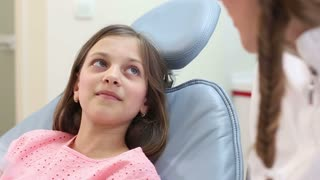 Close up of cute girl sitting in dental chair and listening to dentist