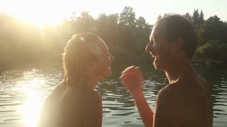 Close up of cute happy couple laughing and talking while sitting by the Mreznica river at sunset, graded