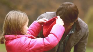 Close up of cute little girl putting her red cap on dad's head , slow motion, graded