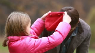 Close up of cute little girl putting her red cap on dad's head
