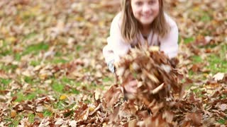 Close up of cute young girl throwing leaves in park in autumn