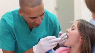 Close up of dental assistant examining teeth of little girl