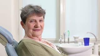 Close up of elderly woman giving thumbs up at dental ordination