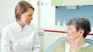 Close up of female dentist and elderly female patient talking