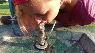 Close up of female longboarder drinking water from public park fountain