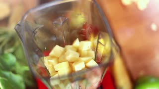 Close-up of hands putting pieces of pineapple in blender, top view, graded