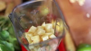 Close-up of hands putting pieces of pineapple in blender, top view