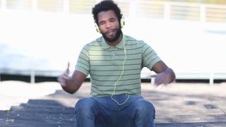 Close up of handsome african american man with headphones listening to music and singing