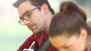 Close-up of handsome man playing guitar and singing while woman sitting next to him, graded