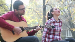 Close-up of handsome man playing guitar while beautiful young woman singing, sitting next to him on bench in park