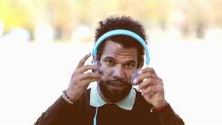 Close up of handsome man putting on blue headphones and listening to music, graded