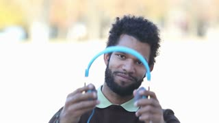 Close up of handsome man putting on blue headphones and listening to music