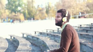 Close up of handsome young man with yellow headphones listening to music, graded
