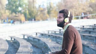 Close up of handsome young man with yellow headphones listening to music