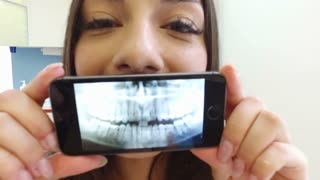 Close up of happy brunette woman holding smartphone with photo of dental X- ray