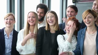 Close up of happy business people, laughing and clapping in office