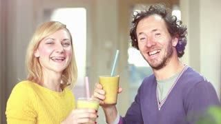 Close-up of happy couple toasting and drinking fruit smoothie, in slow motion, graded